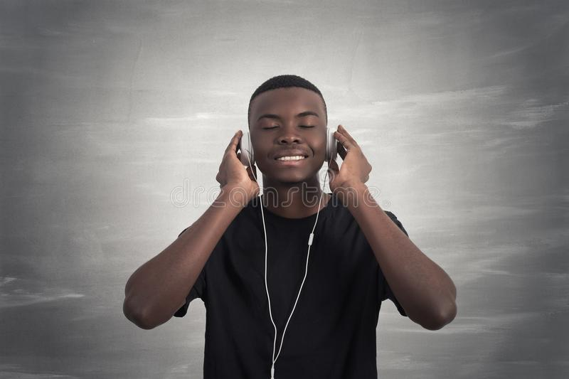 Happy african man smiling listening to music in headphones. Grey background. stock photos