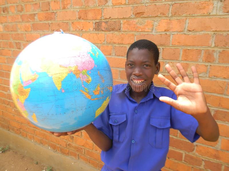 Happy African schoolkid waving hand whilst holding globe map. stock photos