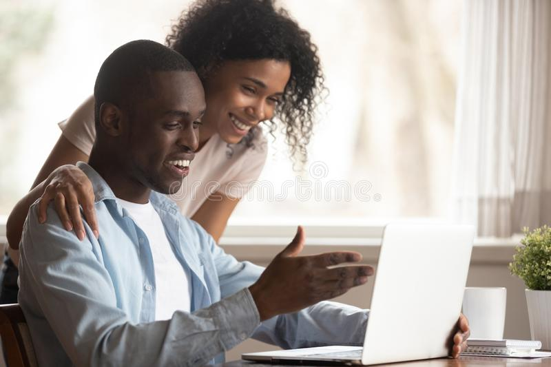 African spouses look at computer screen having fun at home stock photography
