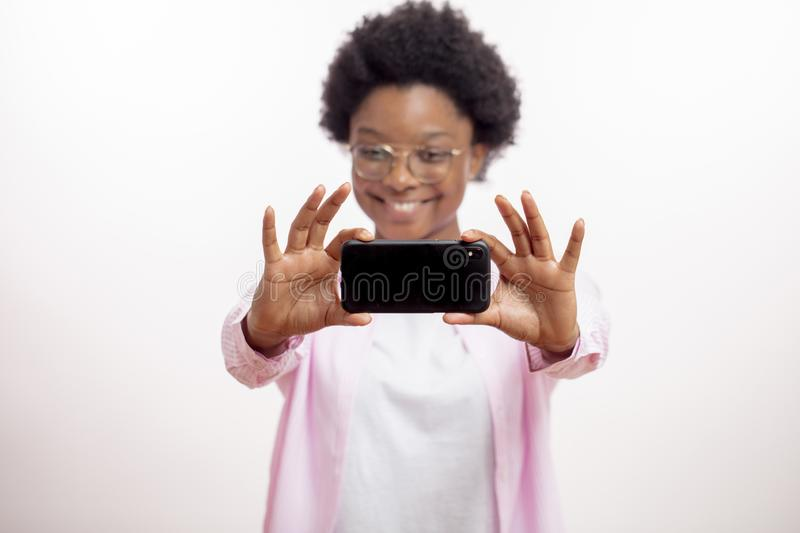 Happy african student is having a video conversation stock image