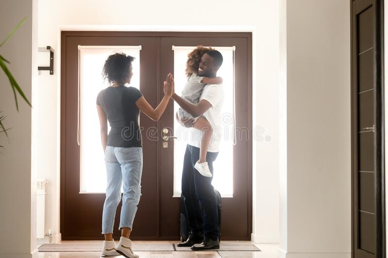 Happy african wife and little daughter meet at doorway father stock photo