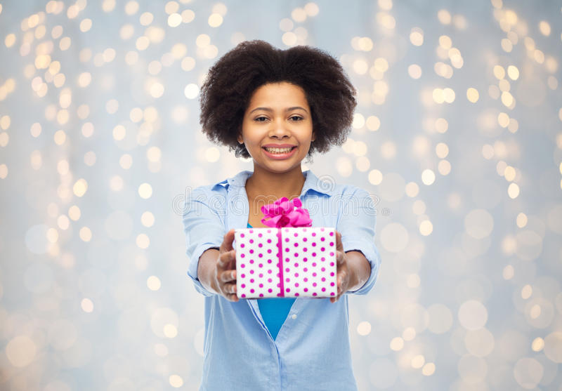 Happy african woman with birthday gift box. People, holidays and greeting concept - happy african american young woman with birthday gift box over holidays stock photography