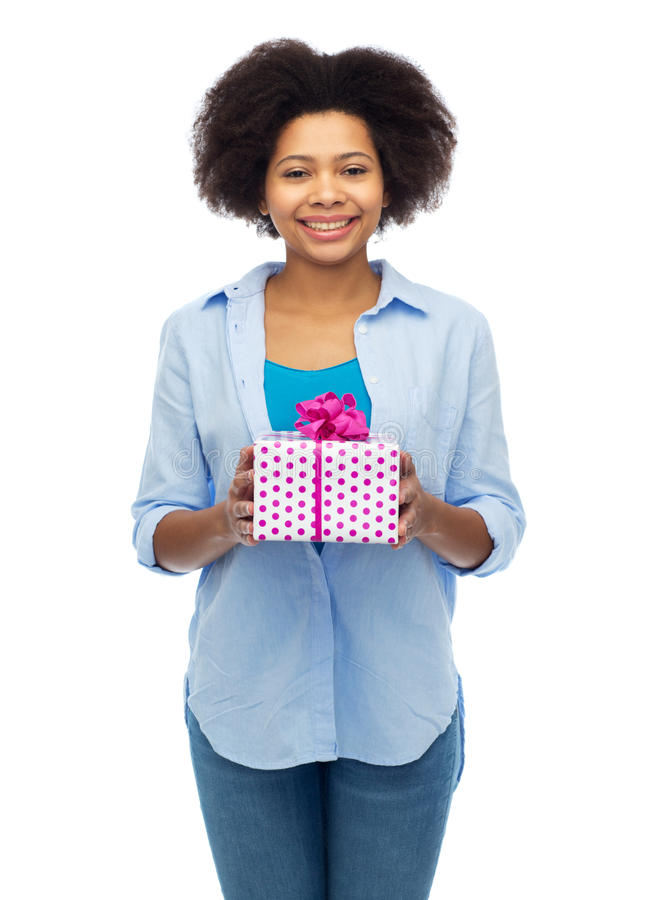 Happy african woman with birthday gift box. People, holidays and greeting concept - happy african american young woman with birthday gift box over white stock photography