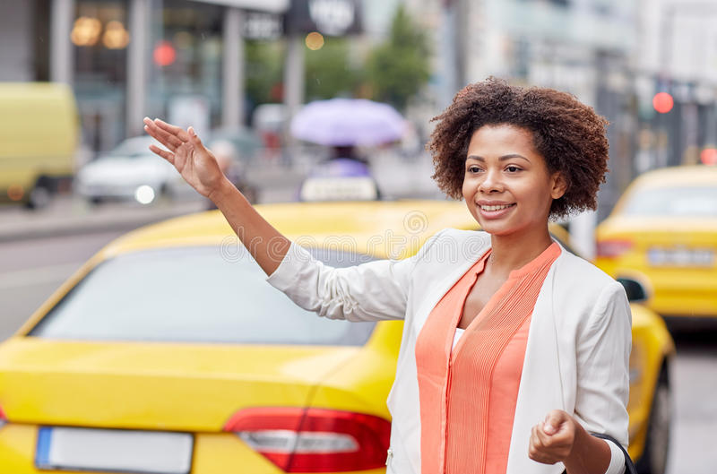 Happy african woman catching taxi royalty free stock photo