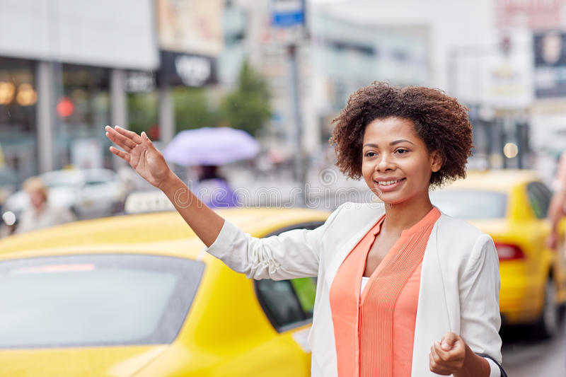 Happy african woman catching taxi stock images