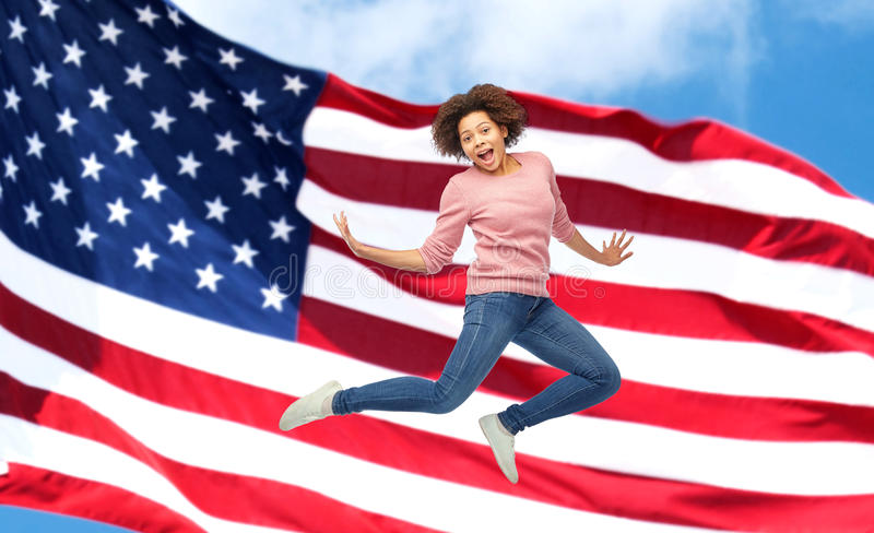 Happy african woman jumping over american flag. People, motion and action concept - happy african young woman jumping over american flag background stock images