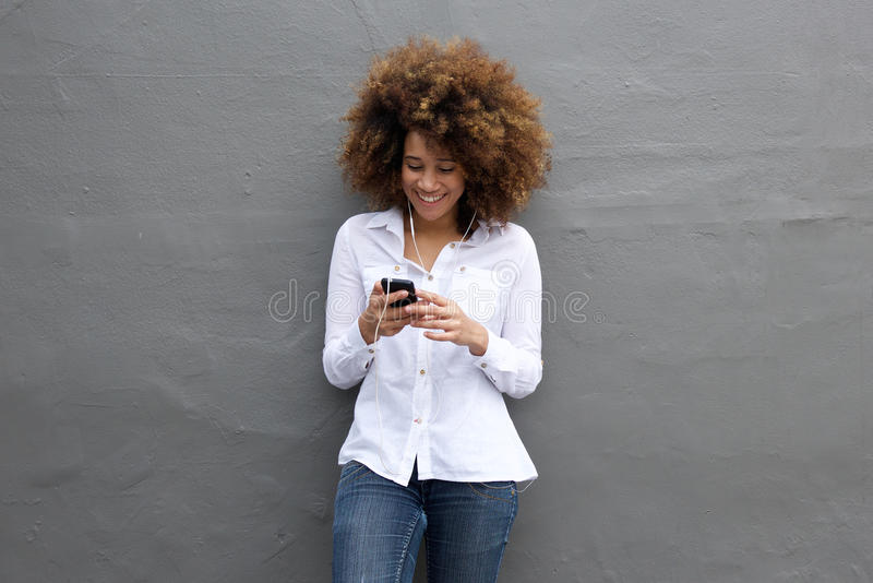 Happy african woman listening music on her cell phone. Portrait of happy young woman listening to music on cell phone stock photo