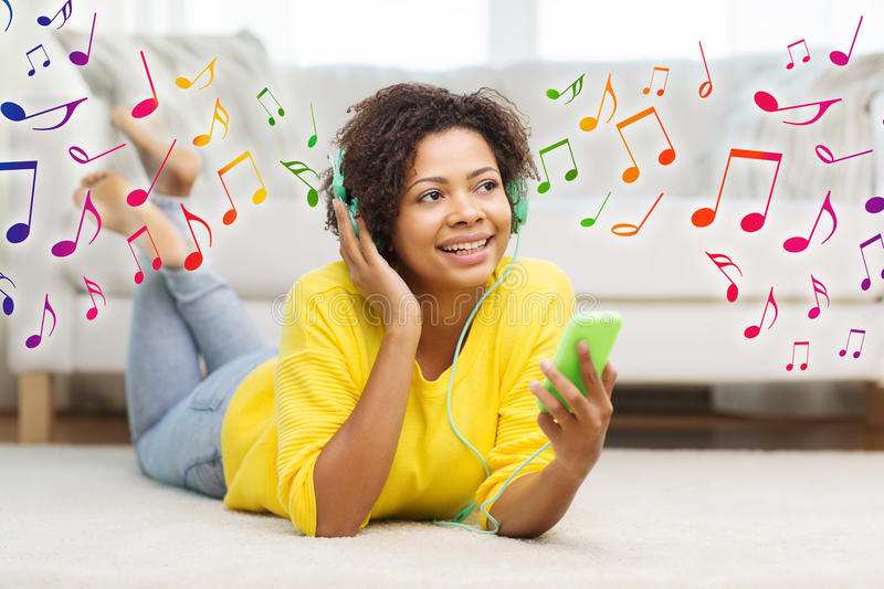 Happy african woman with smartphone and headphones. People, technology and leisure concept - happy african american young woman lying on floor with smartphone stock images