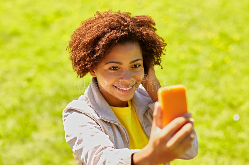 Happy african woman taking selfie with smartphone. Technology, communication and people concept - happy african woman taking selfie with smartphone at summer royalty free stock photo