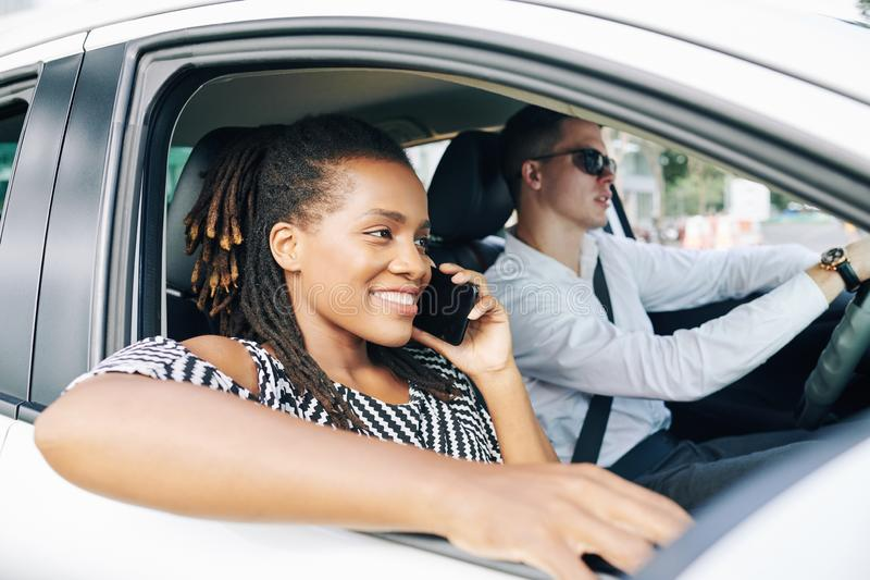 African woman talking on the phone in car stock image