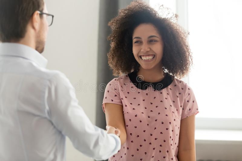 Happy african woman intern worker getting rewarded hired handshaking boss. Happy african women student intern worker getting appreciated rewarded hired promoted stock photos