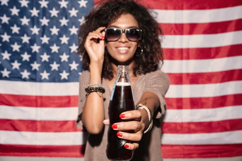 Happy african young lady wearing sunglasses. Picture of happy african young lady wearing sunglasses standing over USA flag drinking aerated water. Looking camera stock image