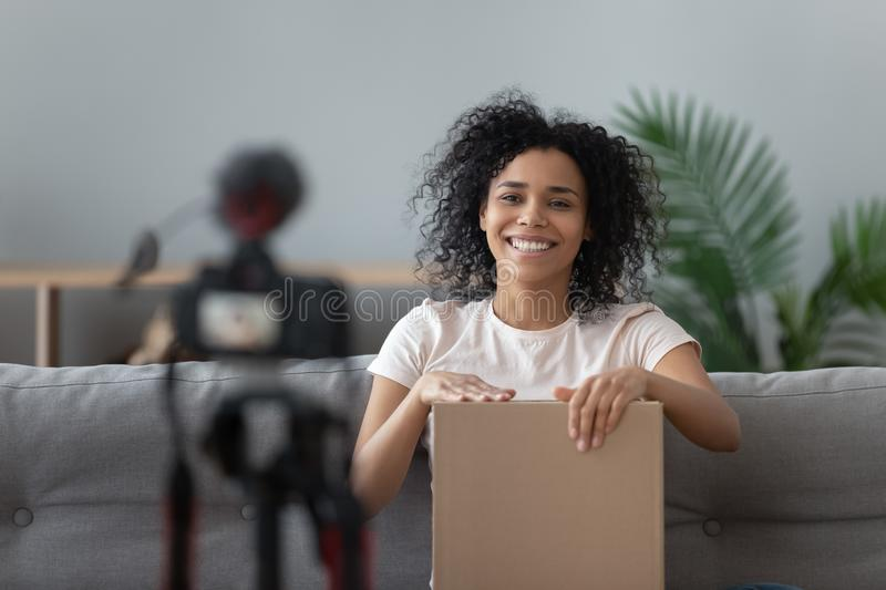 Happy african young woman blogger open parcel shooting video blog stock photo