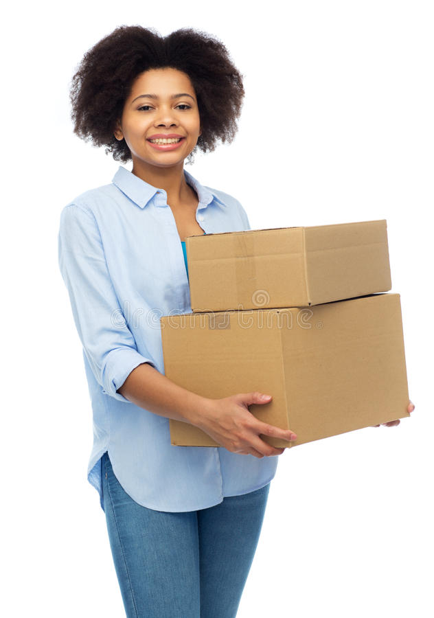 Happy african young woman with parcel boxes. People, delivery, shipping, mail and moving concept - happy african american young woman holding cardboard boxes or stock image