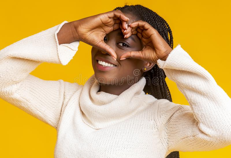 Happy african young woman shaping hands as heart on camera royalty free stock photography