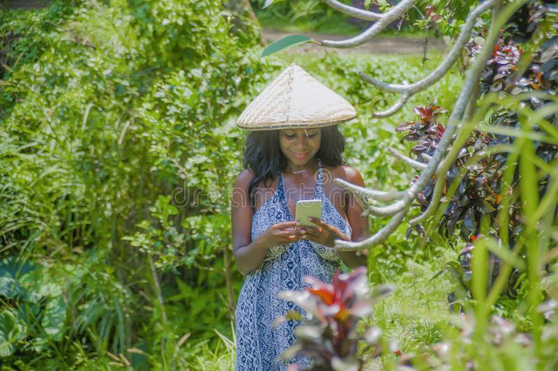 Happy afro american black woman 30s exploring rice fields forest and jungle in Bali wearing rural traditional Asian hat using mobi. Young attractive happy afro royalty free stock images