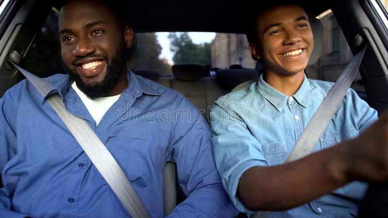 Happy afro-american father and teen sitting in car, dad pleased with sons drive stock photography