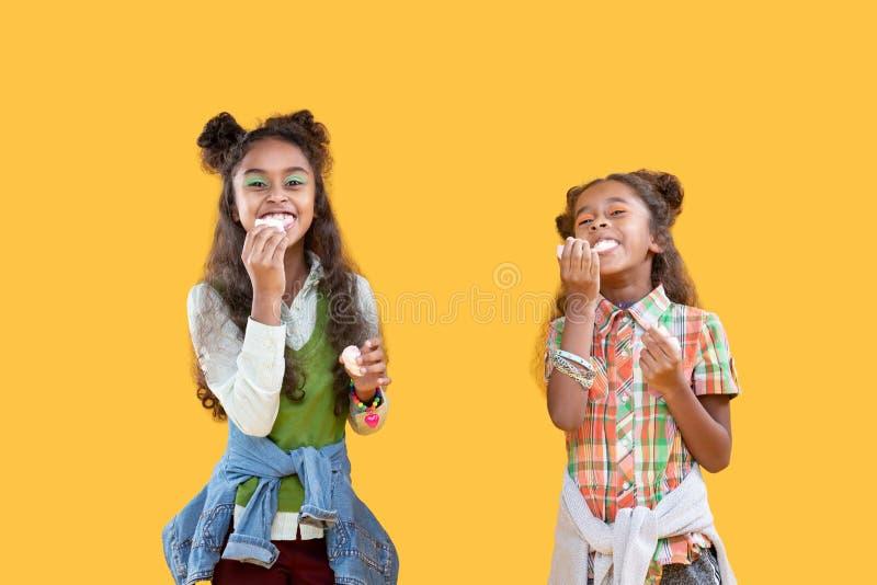 Happy afro American girls enjoying eating sweets stock image