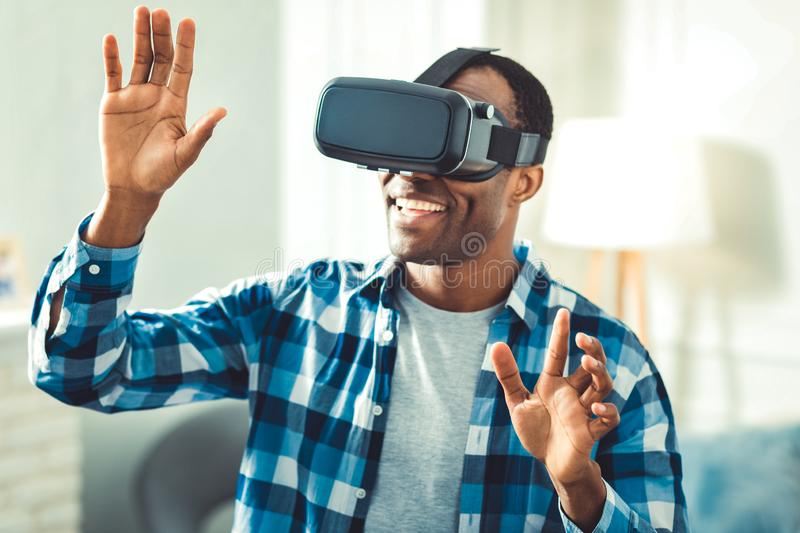Happy afro american man using VR glasses. Next dimension. Exuberant afro american man putting on VR glasses and viewing possibilities royalty free stock photos