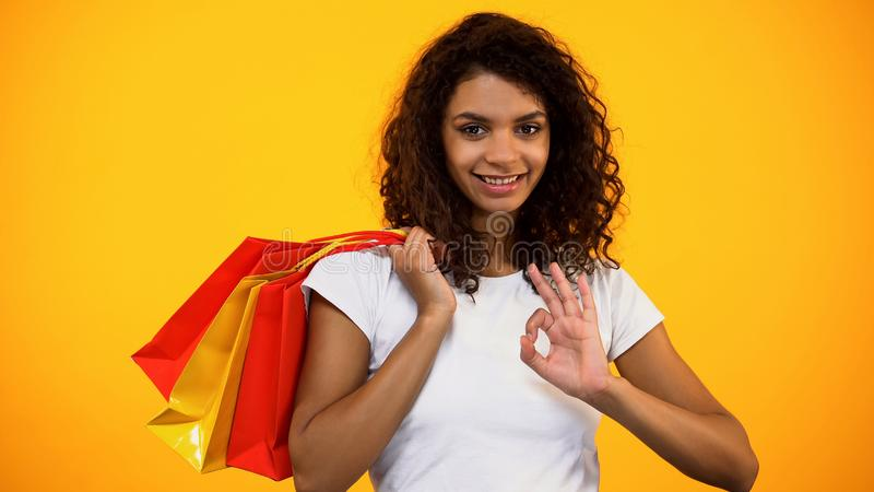 Happy Afro-American woman holding shopping bags and showing ok gesture, sale stock images