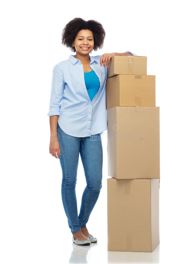 Happy afro american woman with parcel boxes. People, delivery, shipping, mail and moving concept - happy african american young woman with cardboard boxes or stock photo