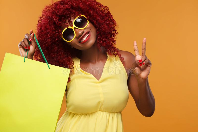 Happy afro american woman at shopping holding yellow bag isolated on orange background on black friday holiday. Copy royalty free stock photo