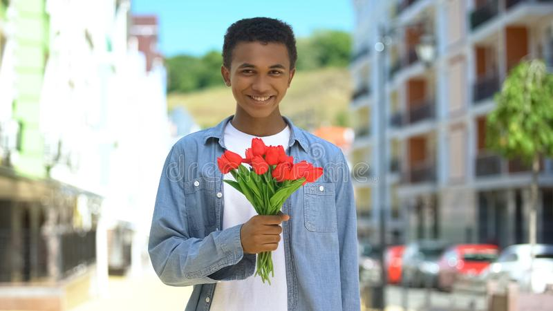 Happy afro-american young male holding tulips bouquet and smiling on camera gift royalty free stock photography