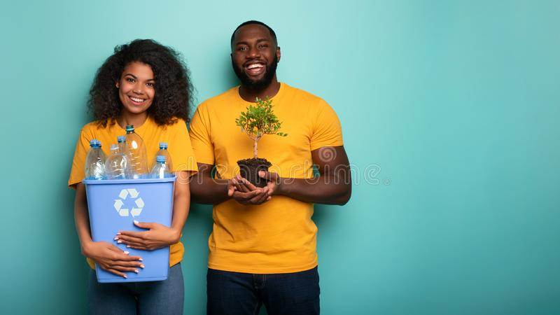 Happy couple hold a plastic container and a small tree over a light blue color. Concept of forestation, ecology. Happy afro couple hold a plastic container and a stock images