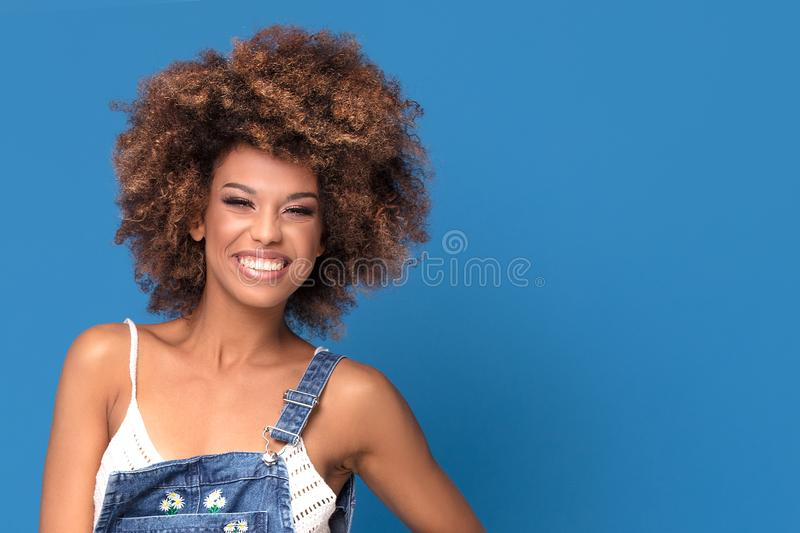 Happy afro girl in jeans dress on blue background. stock photo