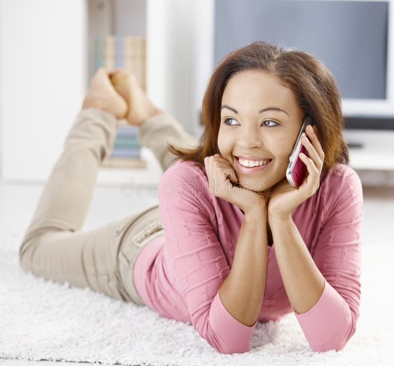 Happy afro girl with mobile phone. Happy afro girl lying on floor using mobile phone, smiling royalty free stock photos