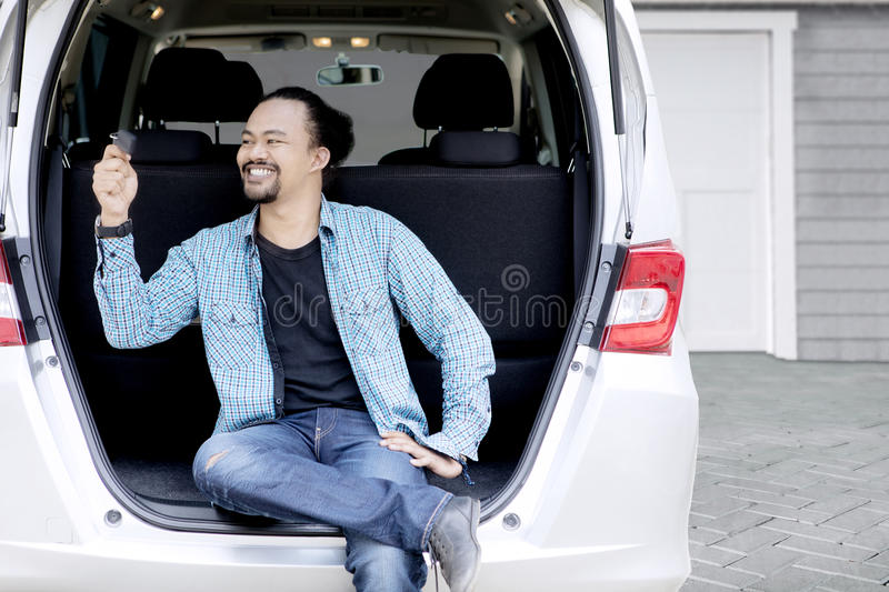 Happy Afro man twisting his car key. Picture of Afro man looks happy while twisting new car key and sitting behind his car royalty free stock photography