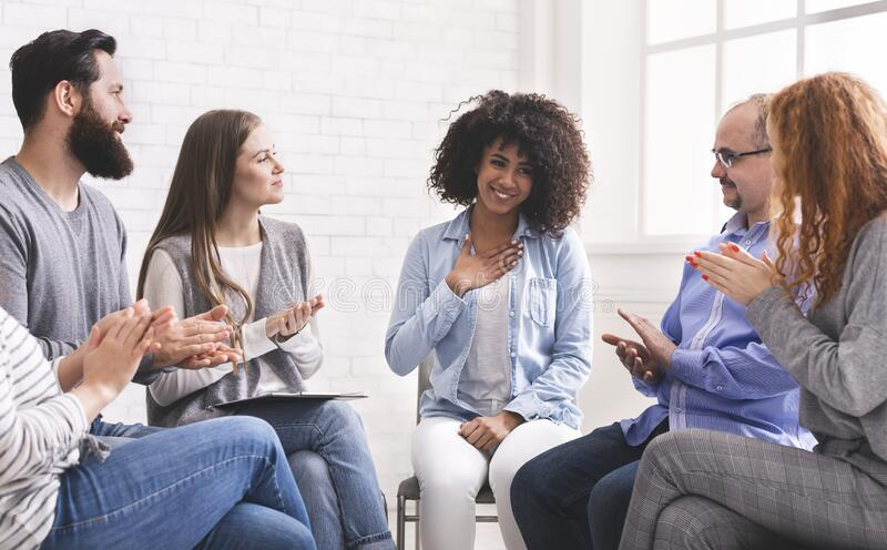 Happy afro woman appreciating support of people at rehab group meeting royalty free stock image