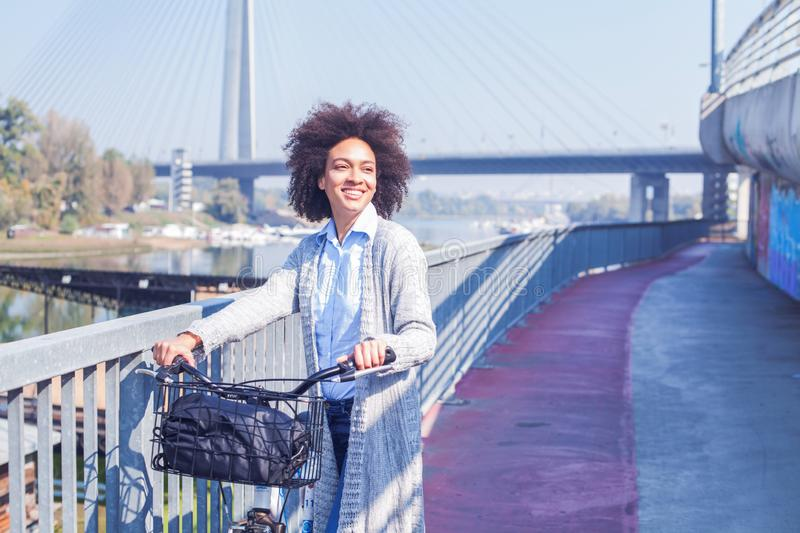 Happy Afro woman with bicycle outdoor portrait royalty free stock photo