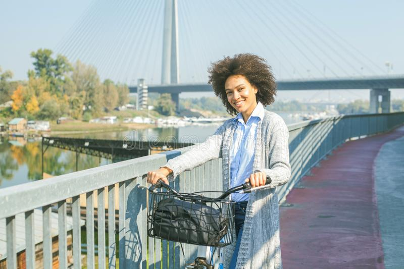 Happy Afro woman with bicycle outdoor portrait stock photo
