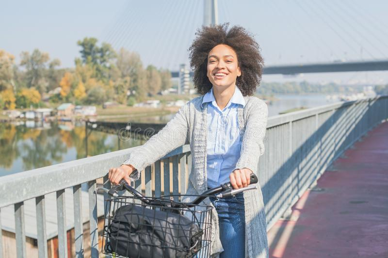 Happy Afro woman with bicycle outdoor portrait royalty free stock photography