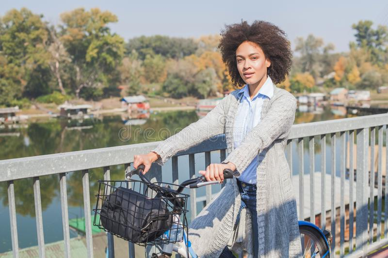 Happy Afro woman with bicycle outdoor portrait stock photography