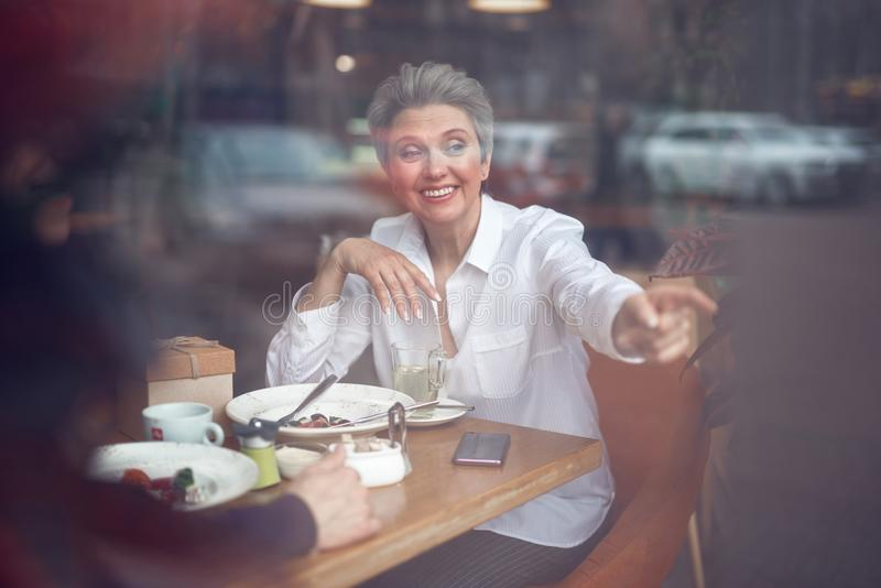 Happy aged lady pointing outside sitting in cafe stock photography