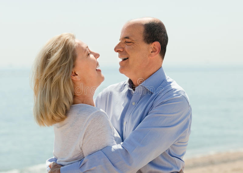 Happy aged lovers laughting outdoor. On seaside stock image