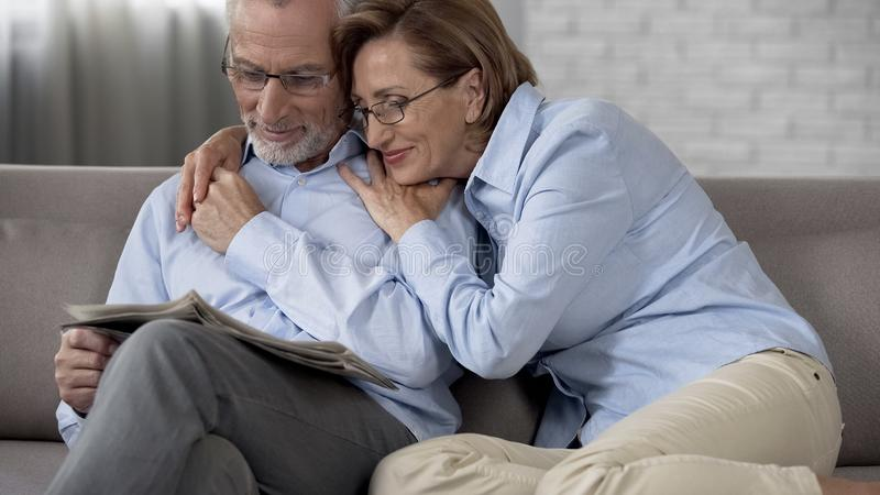 Happy aged man and lady sitting on couch, man reading newspaper wife hugging him royalty free stock image