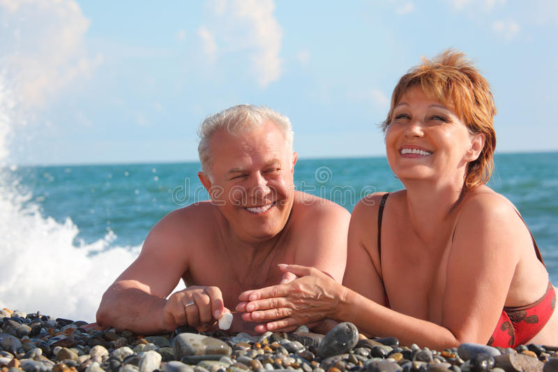 Happy aged pair lie on pebble beach royalty free stock photography