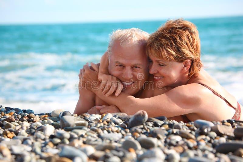 Happy aged pair lie on pebble beach royalty free stock photos