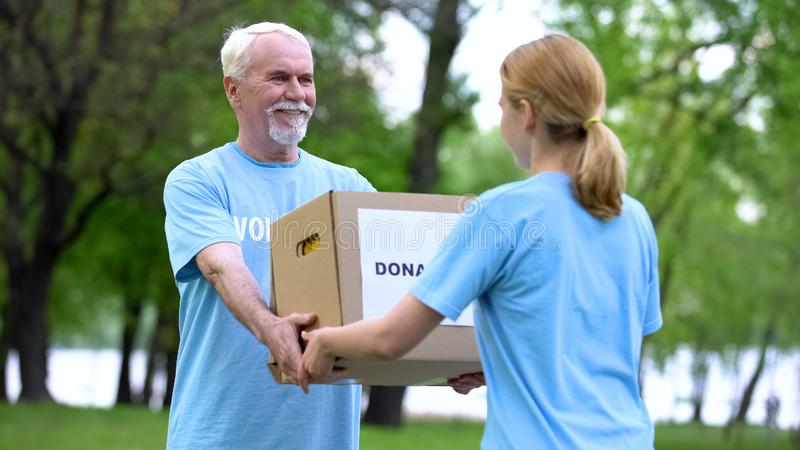 Happy aged volunteer giving donation box young woman, humanitarian aid, charity royalty free stock photography