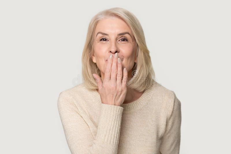 Happy aged woman isolated on grey background send air kiss. Happy positive aged Caucasian woman in sweater isolated on grey studio background look at camera send royalty free stock photography
