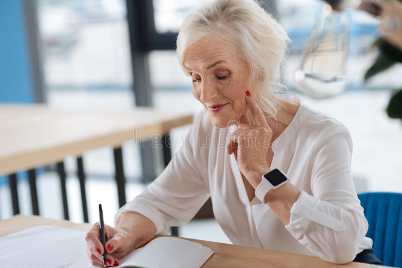 Happy aged woman writing down her memories stock image