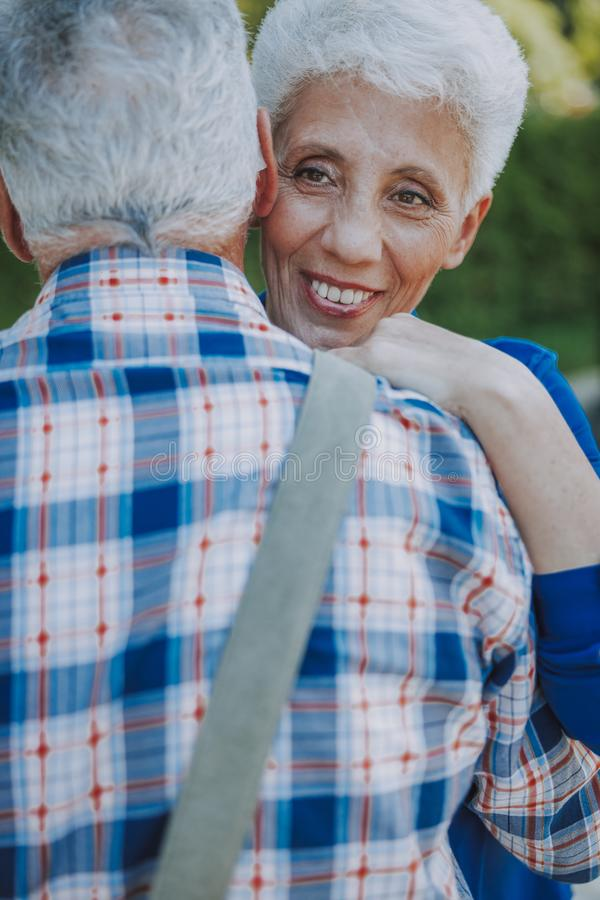 Pleased mature woman hugging her man stock photo stock photo
