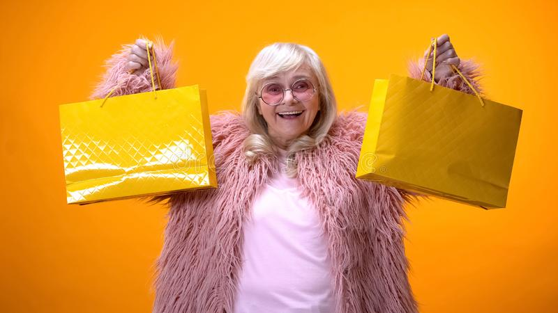 Happy aging lady in funny pink coat showing yellow shopping bags, wasting money royalty free stock photography