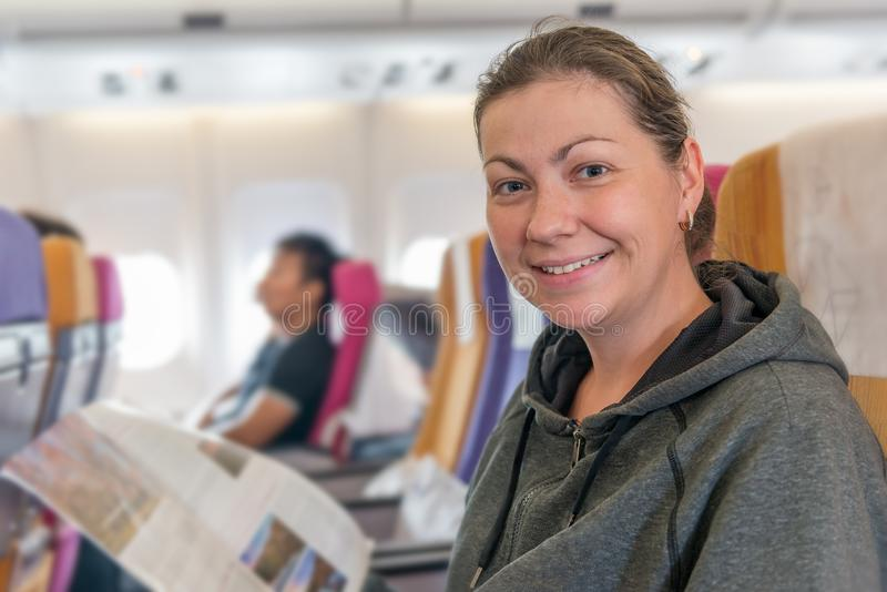 Happy airplane passenger with magazine in chair smiling during f royalty free stock image