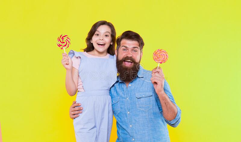 Happy all day. Happy family yellow background. Happy father and daughter eat lollipops. Candy shop. Having fun. Being. Positive. Leisure and rest time. Enjoying stock photos