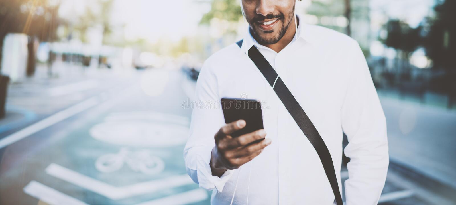Happy american African man using smartphone outdoor.Portrait of young black cheerful man texting a sms message while royalty free stock photo
