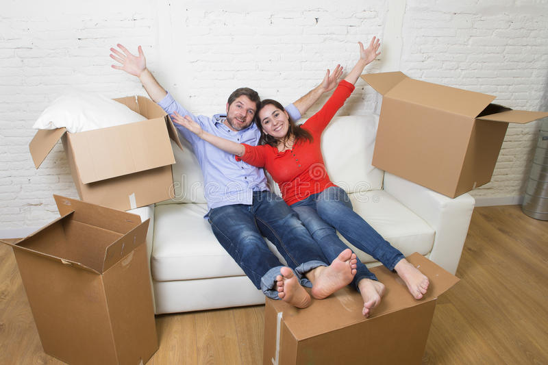 Happy American couple lying on couch together celebrating moving in new house flat or apartment royalty free stock photography